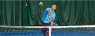 male asian player hitting a tennis ball