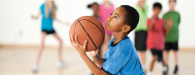 a male boy is shooting a basketball