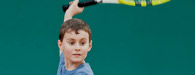 young boy holding tennis racquet